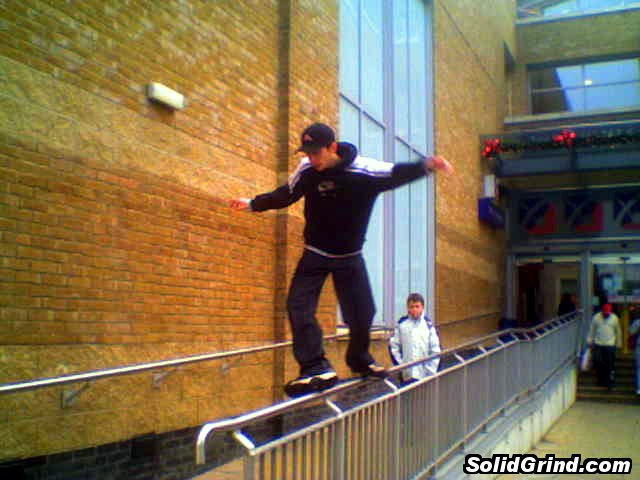 Stuart Pickston doing a cheesegrater on the Chimes shopping centre long rail